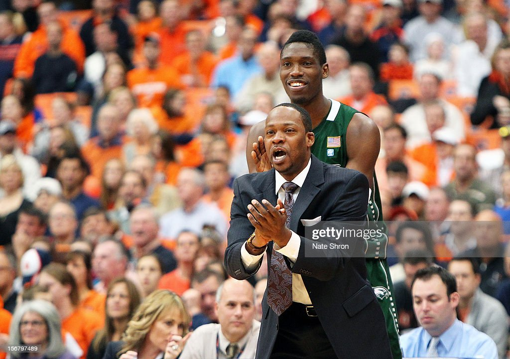 Head coach Bashir Mason of the Wagner Seahawks cheers from the sideline in front of Naofall Folahan #5 during the game against the Syracuse Orange at the Carrier Dome on November 18, 2012 in Syracuse, New York.