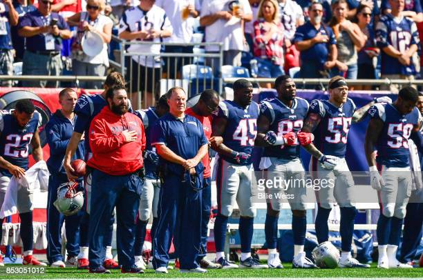 Head coach Bill Belichick looks on as members of the New England Patriots kneel on the sidelines as the National Anthem is played before a game...