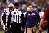 Head coach Bill Belichick of the New England Patriots talks with a referee during their game against the New York Jets at MetLife Stadium on December...