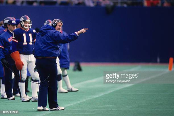 Head coach Bill Parcells of the New York Giants points from the sideline as quarterback Phil Simms looks on during a game against the St Louis...