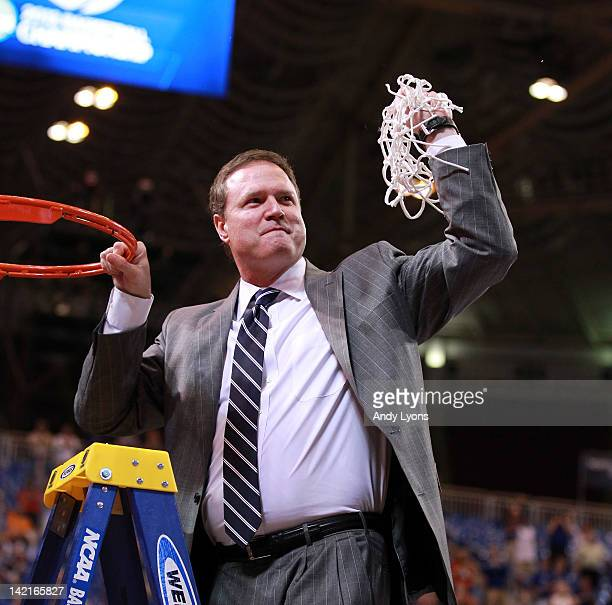 Head coach Bill Self of the Kansas Jayhawks celebrates after cutting down a piece of the net after winning 8067 against the North Carolina Tar Heels...