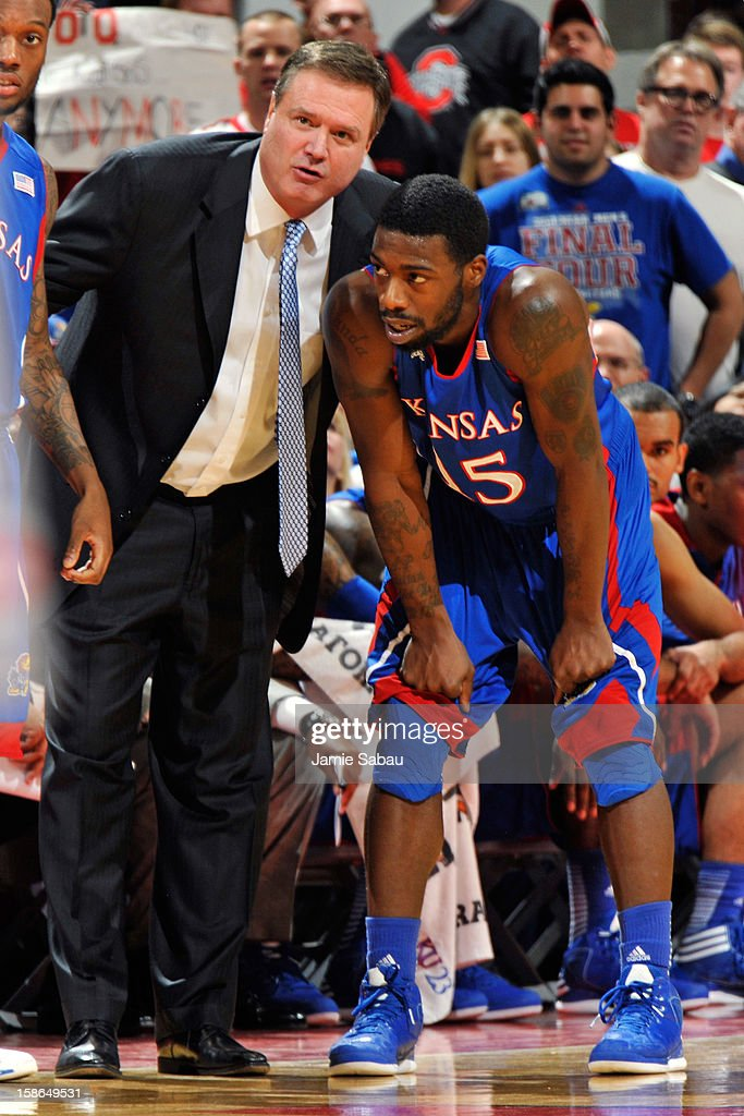 Head coach Bill Self of the Kansas Jayhawks talks with Elijah Johnson #15 of the Kansas Jayhawks during a timeout in the first half against the Ohio State Buckeyes on December 22, 2012 at Value City Arena in Columbus, Ohio.