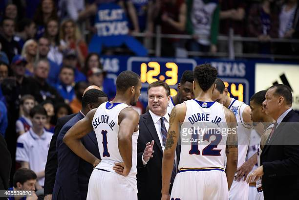 Head coach Bill Self of the Kansas Jayhawks talks with his team during a timeout during a game against the Texas Longhorns at Allen Fieldhouse on...