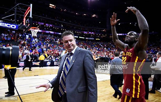 Head coach Bill Self of the Kansas Jayhawks walks off of the court as Dustin Hogue of the Iowa State Cyclones celebrates their 70 to 66 win over the...