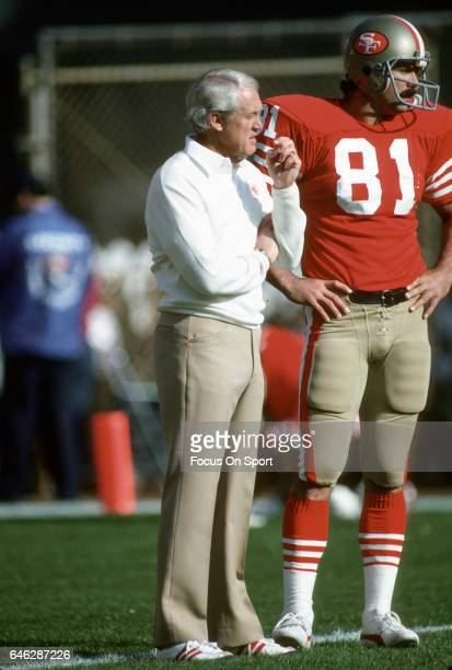 Head coach Bill Walsh of the 'nSan Francisco 49ers talks with tight end Russ Francis during pregame warm ups prior to the start of an NFL Football...