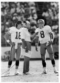 Head coach Bill Walsh of the San Francisco 49ers talks to quarterback Steve Young as quarterback Joe Montana looks on during the game against the...