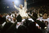 Head Coach Bill Walsh of the San Francisco 49ers with his hands rised high is carried on the shoulders of two of his players after the 49ers defeated...