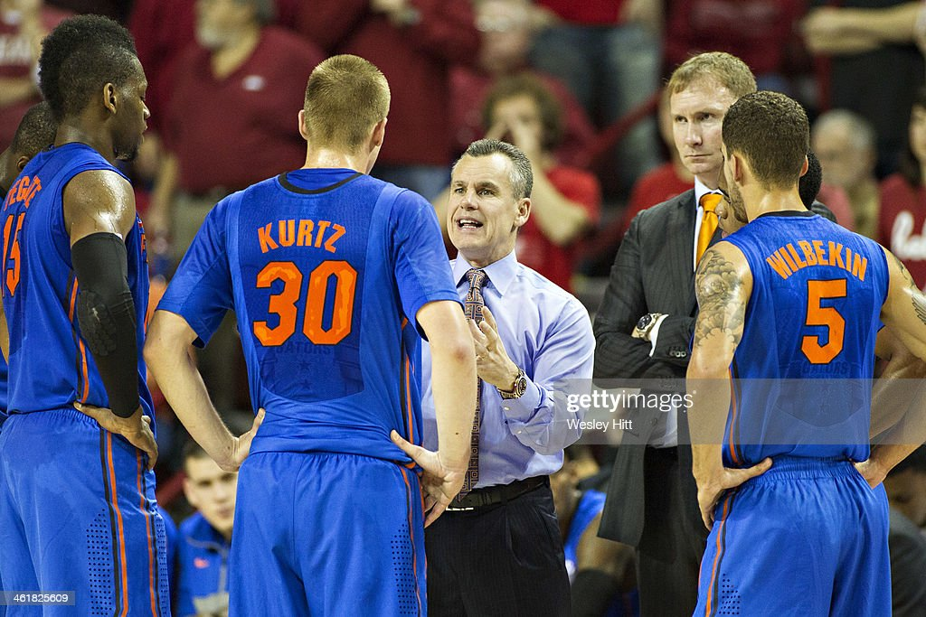 Head Coach Billy Donovan talks with Jacob Kurtz #30 of the Florida Gators during a timout against the Arkansas Razorbacks at Bud Walton Arena on January 11, 2014 in Fayetteville, Arkansas. The Gators defeated the Razorbacks 84-82.