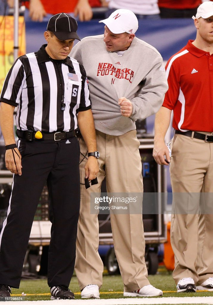 Head coach Bo Pelini talks with a official while playing the Wisconsin Badgers in the Big 10 Conference Championship Game at Lucas Oil Stadium on December 1, 2012 in Indianapolis, Indiana.