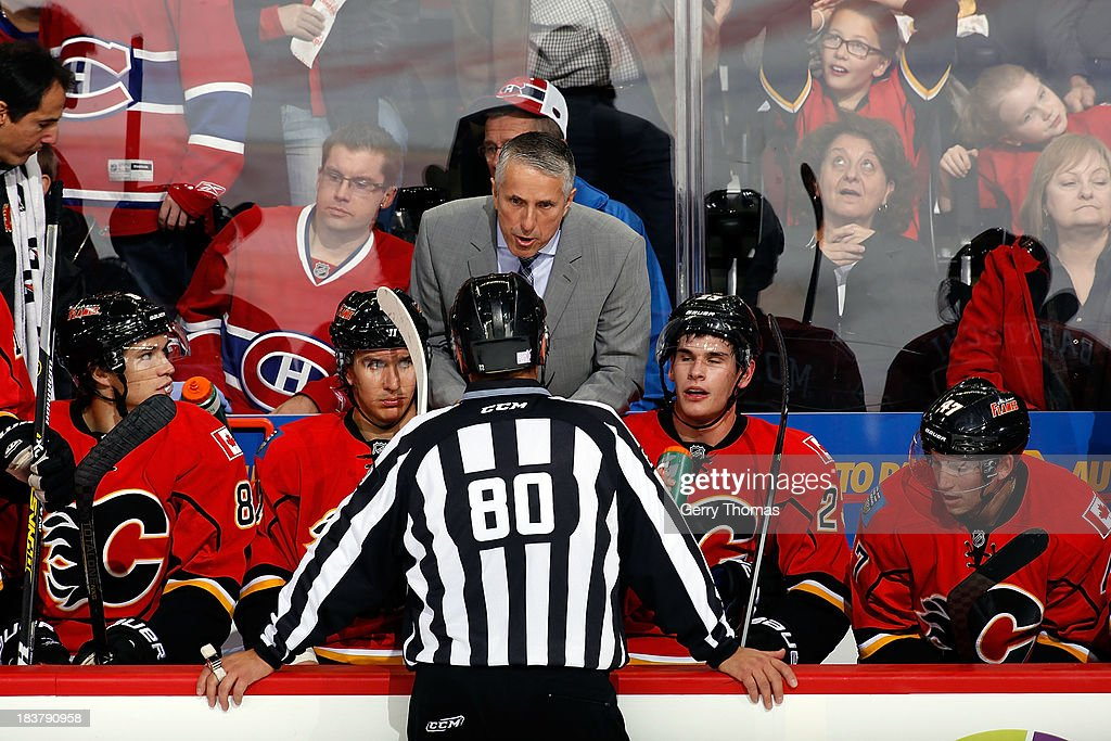Head coach Bob Hartley of the Calgary Flames has a discussion with a referee during a stoppage in play against the Montreal Canadiens at Scotiabank Saddledome on October 9, 2013 in Calgary, Alberta, Canada.