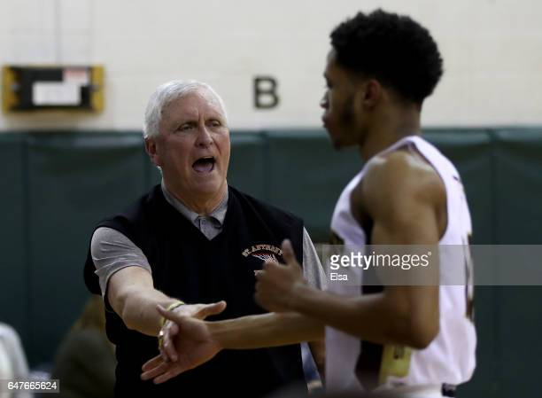 Head coach Bob Hurley of the St Anthony Friars congratulates one of his players as they head for the bench in the second half against the Monclair...