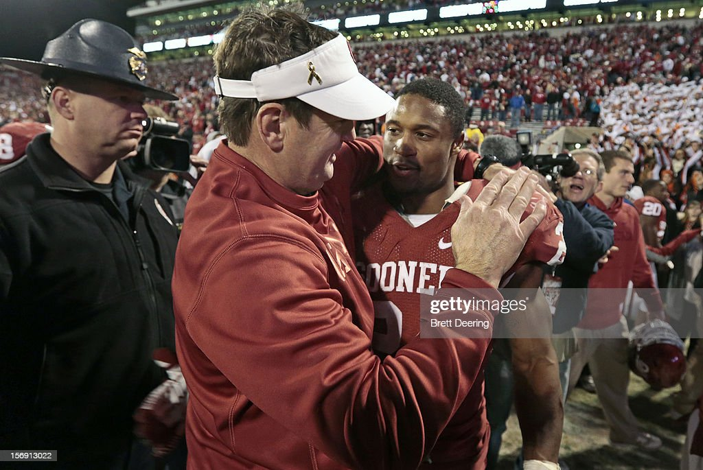Head Coach <a gi-track='captionPersonalityLinkClicked' href=/galleries/search?phrase=Bob+Stoops&family=editorial&specificpeople=241307 ng-click='$event.stopPropagation()'>Bob Stoops</a> and running back Brennan Clay #24 of the Oklahoma Sooners celebrate after the game against the Oklahoma State Cowboys November 24, 2012 at Gaylord Family-Oklahoma Memorial Stadium in Norman, Oklahoma. Oklahoma defeated Oklahoma State 51-48 in overtime.
