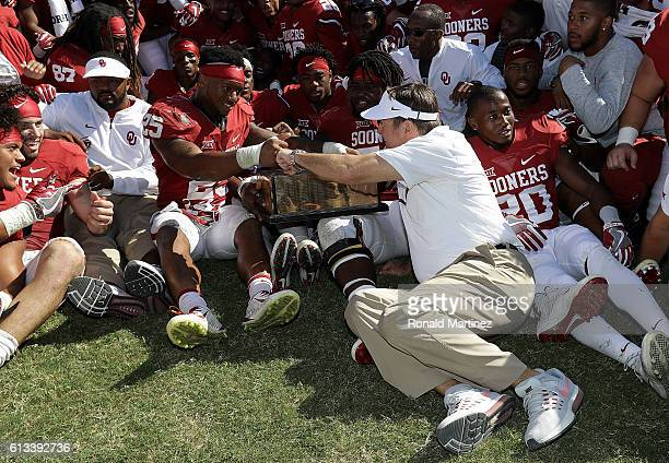 Head coach Bob Stoops bumps fists with Joe Mixon of the Oklahoma Sooners after a 4540 win against the Texas Longhorns at Cotton Bowl on October 8...