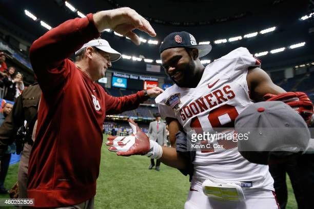 Head coach Bob Stoops celebrates with Eric Striker of the Oklahoma Sooners after defeating the Crimson Tide 4531 to win the Allstate Sugar Bowl at...