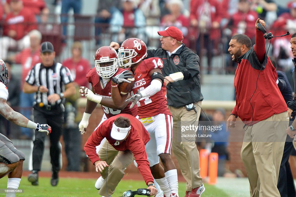 Head coach <a gi-track='captionPersonalityLinkClicked' href=/galleries/search?phrase=Bob+Stoops&family=editorial&specificpeople=241307 ng-click='$event.stopPropagation()'>Bob Stoops</a>, defensive coordinator Mike Stoops and defensive line coach Jerry Montgomery of the Oklahoma Sooners run on the field to protest a call while <a gi-track='captionPersonalityLinkClicked' href=/galleries/search?phrase=Bob+Stoops&family=editorial&specificpeople=241307 ng-click='$event.stopPropagation()'>Bob Stoops</a> gets hit by cornerback Aaron Colvin #14 of the Oklahoma Sooners during their win against the Texas Tech Red Raiders on October 26, 2013 at Gaylord Family Oklahoma Memorial Stadium in Norman, Oklahoma.