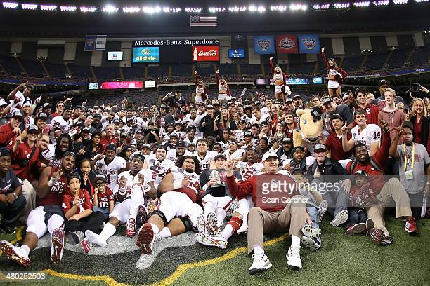 Head coach Bob Stoops of the Oklahoma Sooners celebrates with his team and the winner's trophy after defeating the Alabama Crimson Tide 4531 during...