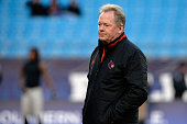 Head coach Bobby Petrino of the Louisville Cardinals watches his team warm up before a game against the Georgia Bulldogs at the Belk Bowl at Bank of...