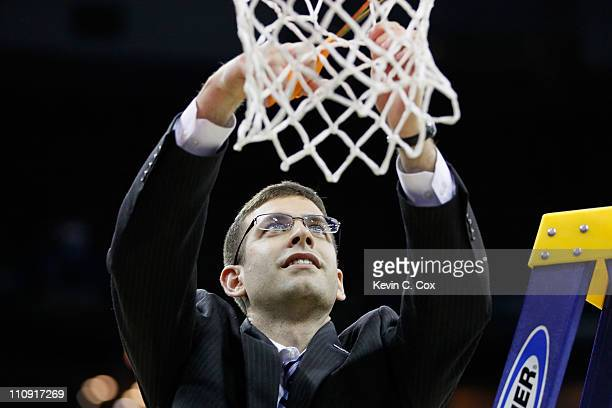 Head coach Brad Stevens of the Butler Bulldogs celebrates defeating the Florida Gators 74 to 71 in overtime by cuttin down part of the net during the...