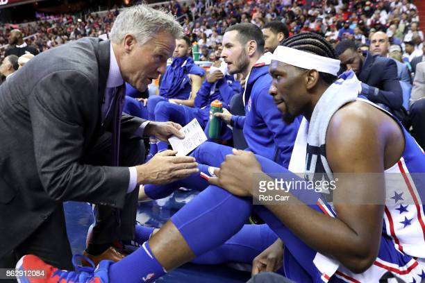 Head coach Brett Brown of the Philadelphia 76er talks with Joel Embiid in the first half against the Washington Wizards at Capital One Arena on...