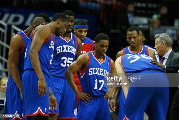 Head coach Brett Brown of the Philadelphia 76ers waits with his team near the bench during a timeout during the game against the Houston Rockets at...