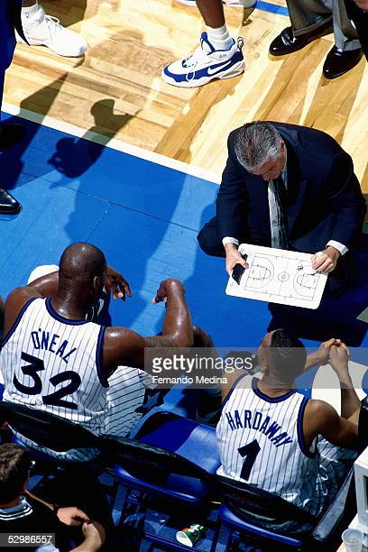 Head Coach Brian Hill of the Orlando Magic charts a play for Shaquille O'Neal and Anfernee Hardaway during a time out against the Chicago Bulls...