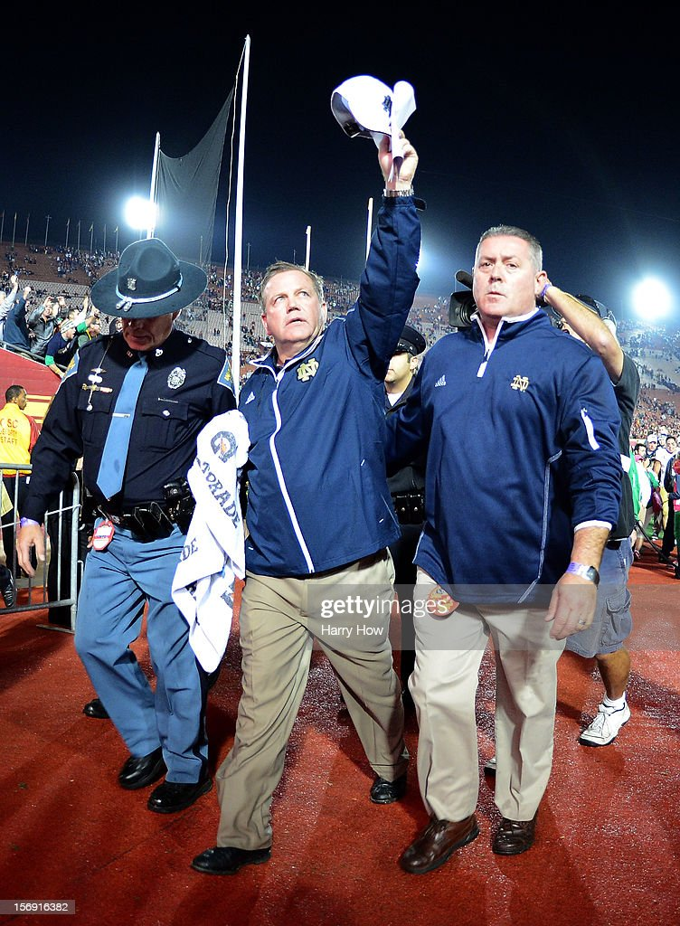 Head Coach Brian Kelly of the Notre Dame Fighting Irish celebrates a 22-13 win over the USC Trojans as he leaves the field at Los Angeles Memorial Coliseum on November 24, 2012 in Los Angeles, California.