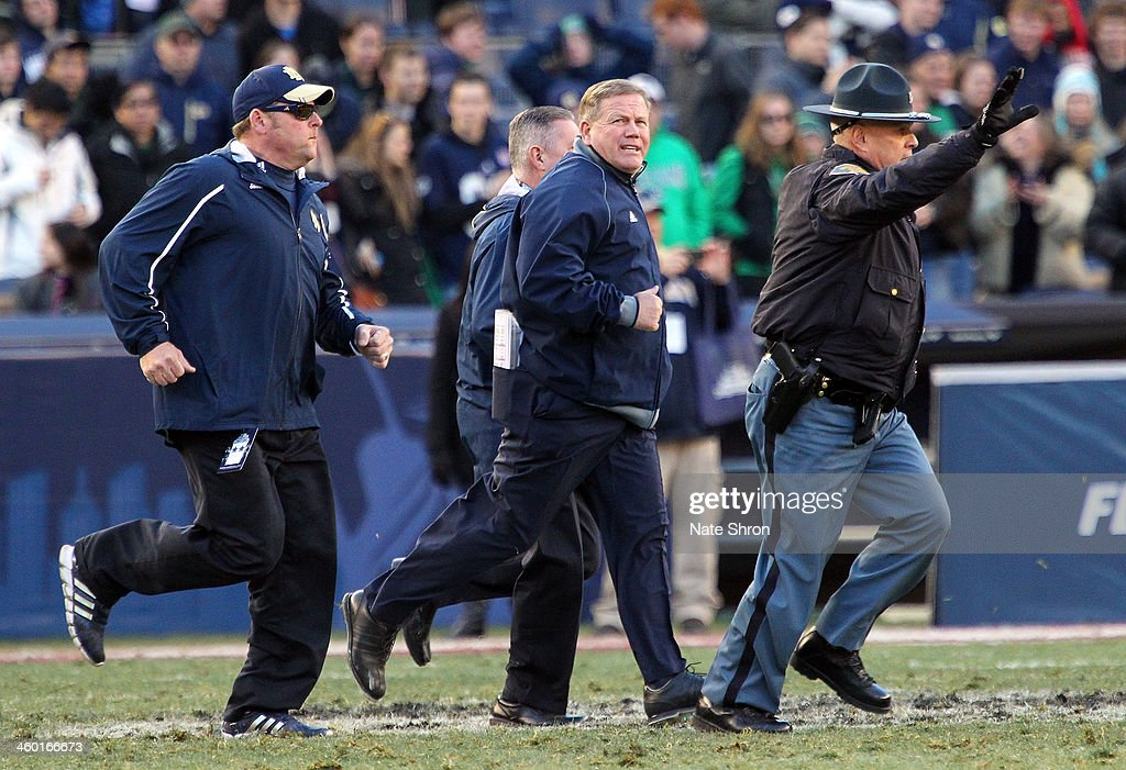 Head coach Brian Kelly of the Notre Dame Fighting Irish jogs off the field during the game against the Rutgers Scarlet Knights during the New Era Pinstripe Bowl at Yankee Stadium on December 28, 2013 in the Bronx Borough of New York City.