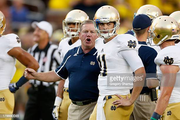 Head coach Brian Kelly of the Notre Dame Fighting Irish talks to quarterback Tommy Rees before the game against the Michigan Wolverines at Michigan...