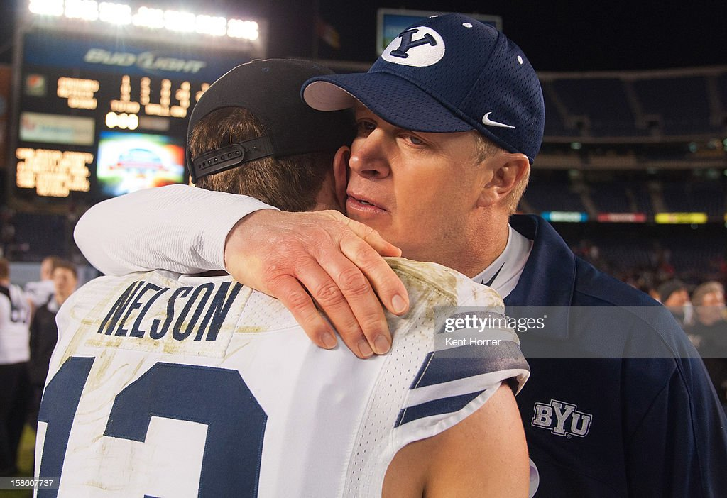 Head coach Bronco Mendenhall of the BYU Cougars hugs quarterback Riley Nelson #13 immediately following the game against the San Diego State Aztecs in the Poinsettia Bowl at Qualcomm Stadium on December 20, 2012 in San Diego, California.