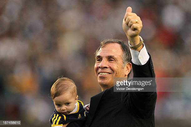 Head coach Bruce Arena of Los Angeles Galaxy waves to the crowd while holding grandson Wade Arena as he walks off the field after the Galaxy defeat...