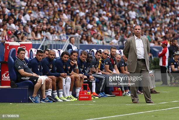 Head Coach Bruce Arena of the Los Angeles Galaxy and his team look on from the bench area during the MLS match between FC Dallas and the Los Angeles...