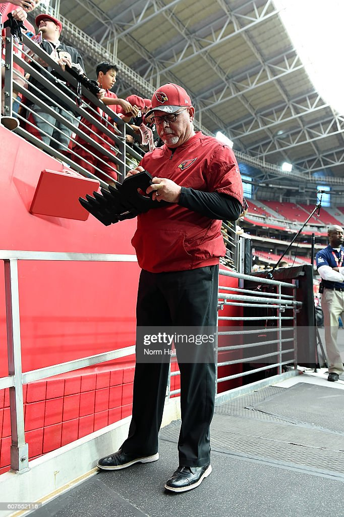 Head coach Bruce Arians of the Arizona Cardinals signs an autograph before the start of the NFL game against the Tampa Bay Buccaneers at University of Phoenix Stadium on September 18, 2016 in Glendale, Arizona.