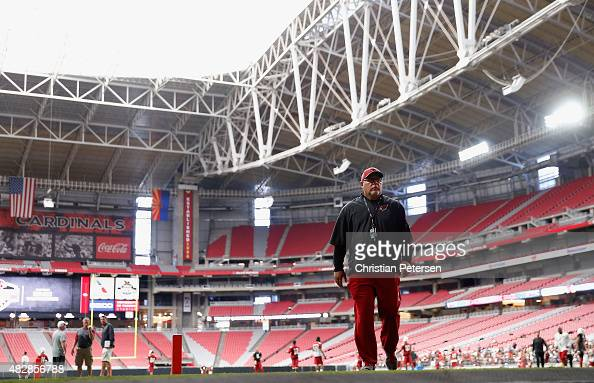 Head coach Bruce Arians of the Arizona Cardinals walks off the field following the team training camp at University of Phoenix Stadium on August 2...