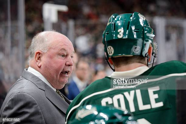 Head coach Bruce Boudreau of the Minnesota Wild speaks with Charlie Coyle on the bench during the game against Winnipeg Jets on October 15 2016 at...