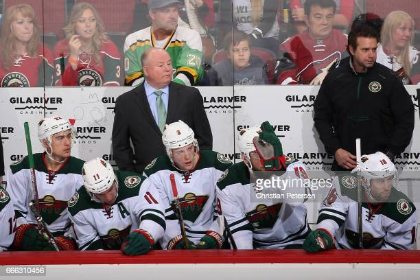 Head coach Bruce Boudreau of the Minnesota Wild watches from the bench during the first period of the NHL game against the Arizona Coyotes at Gila...