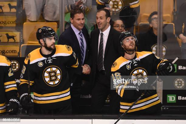 Head Coach Bruce Cassidy and Assistant Coach Jay Pandolfo of the Boston Bruins shake hands after clinching a play off spot against the Tampa Bay...