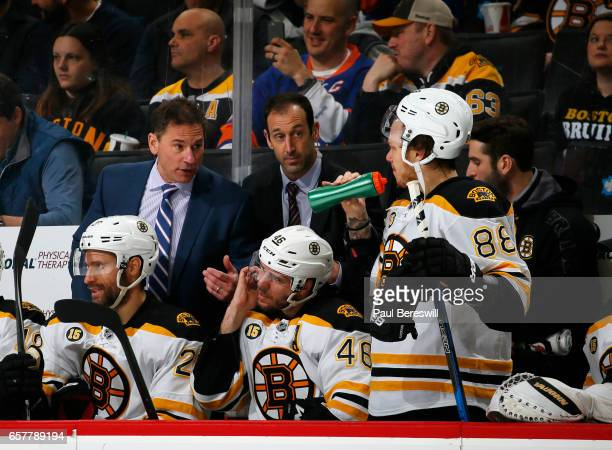 Head coach Bruce Cassidy of the Boston Bruins talks to David Pastrnak during the second period against the New York Islanders at the Barclays Center...