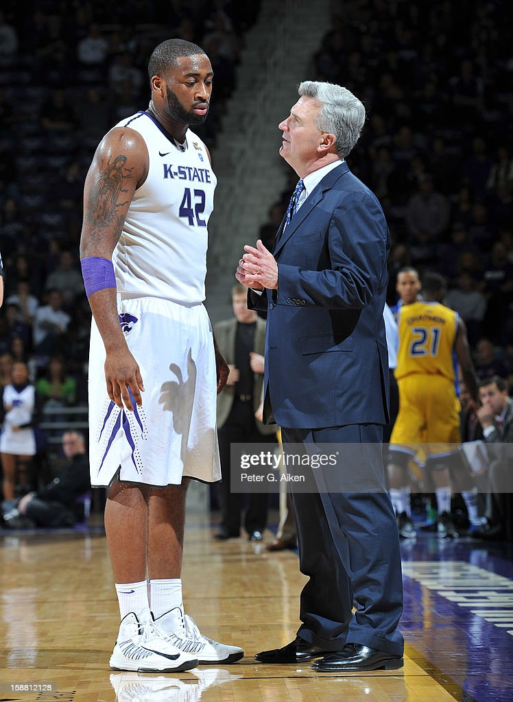 Head coach Bruce Weber (R) of the Kansas State Wildcats talks with forward Thomas Gipson #42 during a time-out against the Missouri-Kansas City Kangaroos in the second half on December 29, 2012 at Bramlage Coliseum in Manhattan, Kansas.