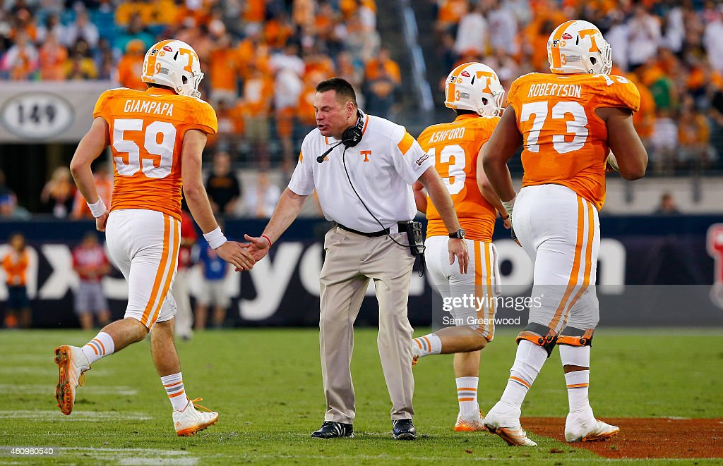 Head coach <a gi-track='captionPersonalityLinkClicked' href=/galleries/search?phrase=Butch+Jones&family=editorial&specificpeople=4501034 ng-click='$event.stopPropagation()'>Butch Jones</a> of the Tennessee Volunteers celebrates with players during the TaxSlayer Bowl against the Iowa Hawkeyes at EverBank Field on January 2, 2015 in Jacksonville, Florida. The Tennessee Volunteers defeated the Iowa Hawkeyes 45-28.