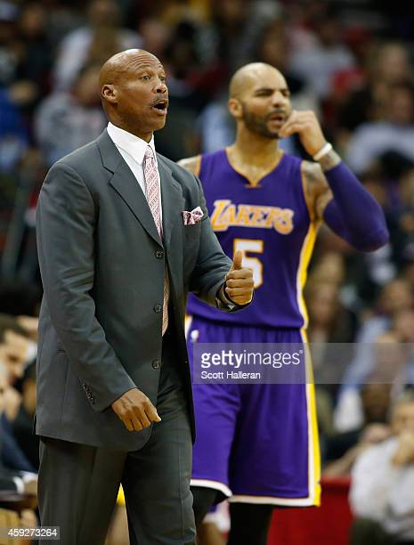 Head coach Byron Scott of the Los Angeles Lakers waits on the court alongside Carlos Boozer during their game against the Houston Rockets at the...