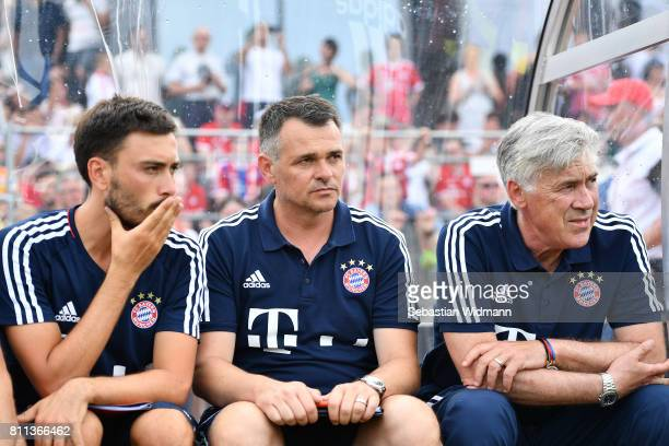 Head coach Carlo Ancelotti assistant coach Willy Sagnol and assistant coach Davide Ancelotti wait for the start of the preseason friendly match...