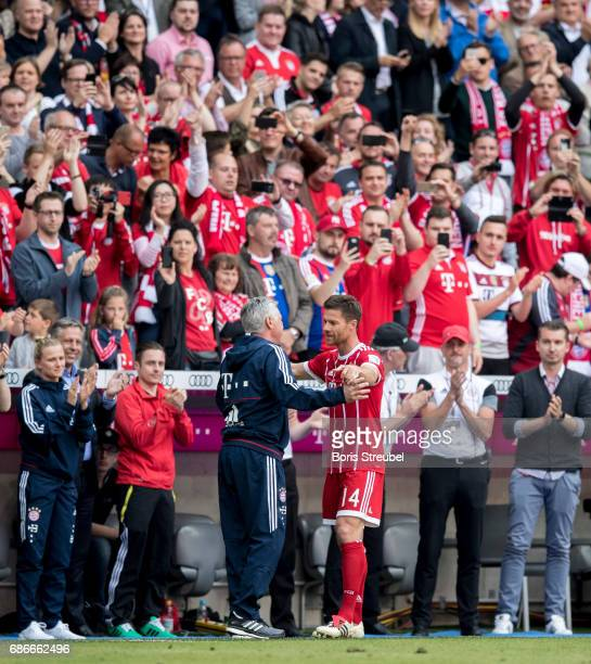 Head coach Carlo Ancelotti of FC Bayern Muenchen hugs Xabi Alonso of FC Bayern Muenchen after his substitution during the Bundesliga match between...