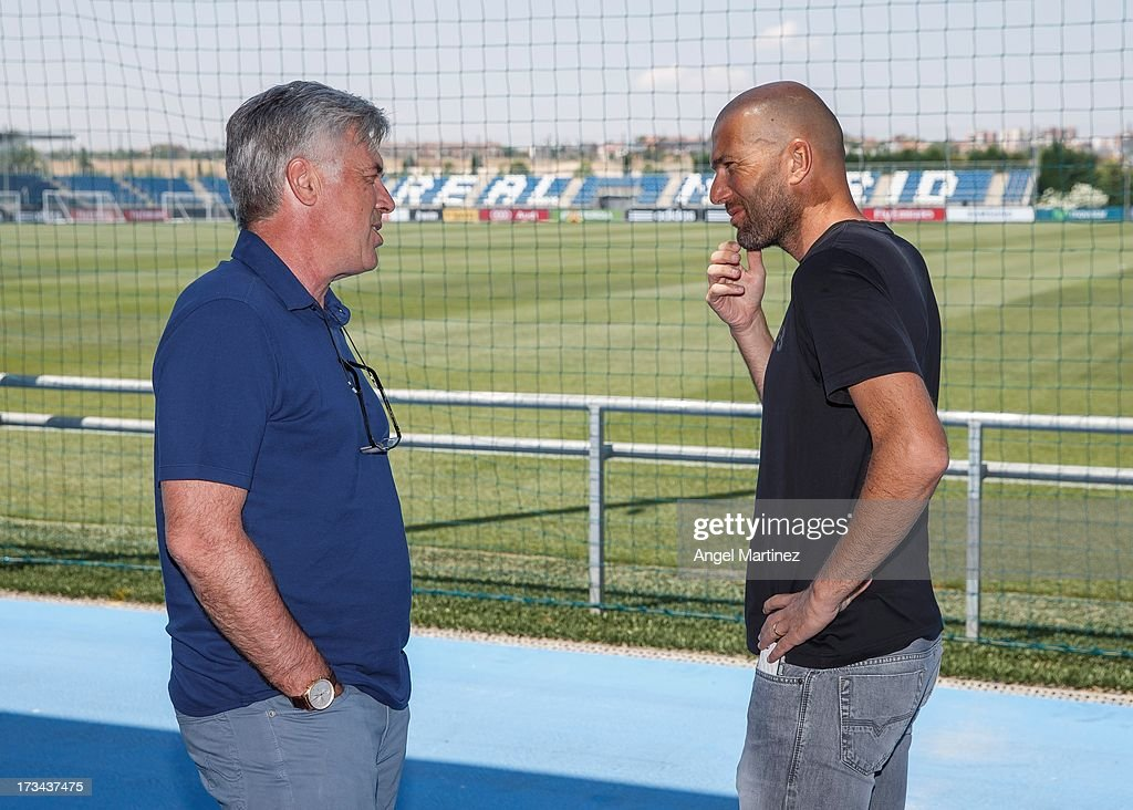 Head coach <a gi-track='captionPersonalityLinkClicked' href=/galleries/search?phrase=Carlo+Ancelotti&family=editorial&specificpeople=226747 ng-click='$event.stopPropagation()'>Carlo Ancelotti</a> (L) of Real Madrid chats with his assistant <a gi-track='captionPersonalityLinkClicked' href=/galleries/search?phrase=Zinedine+Zidane&family=editorial&specificpeople=172012 ng-click='$event.stopPropagation()'>Zinedine Zidane</a> at Valdebebas training ground on July 14, 2013 in Madrid, Spain.