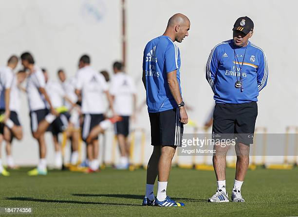 Head coach Carlo Ancelotti of Real Madrid chats with his assistant Zinedine Zidane during a training session at Valdebebas training ground on October...
