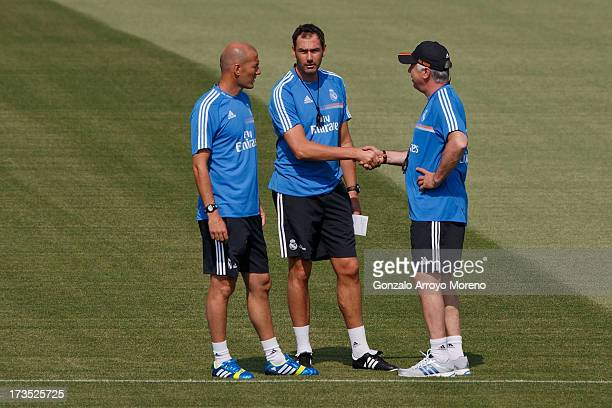 Head coach Carlo Ancelotti of Real Madrid shakes hands with assistant coach Paul Clement as Zinedine Zidane looks them during a training session at...