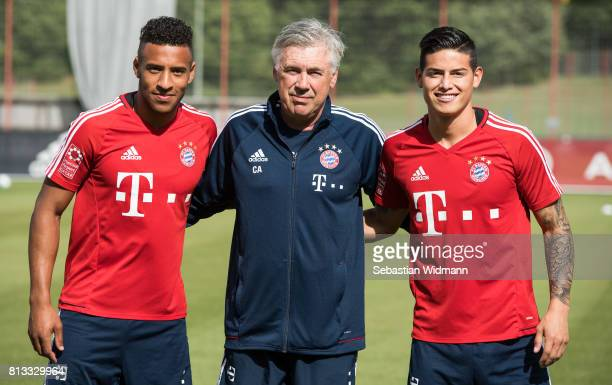 Head coach Carlo Ancelotti poses with Corentin Tolisso and James Rodriguez before a training session at Saebener Strasse training ground on July 12...