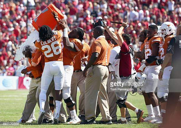 Head coach Charlie Strong of the Texas Longhorns is soakes with the water cooler as the Longhorns beat the Oklahoma Sooners 2417 during the ATT Red...