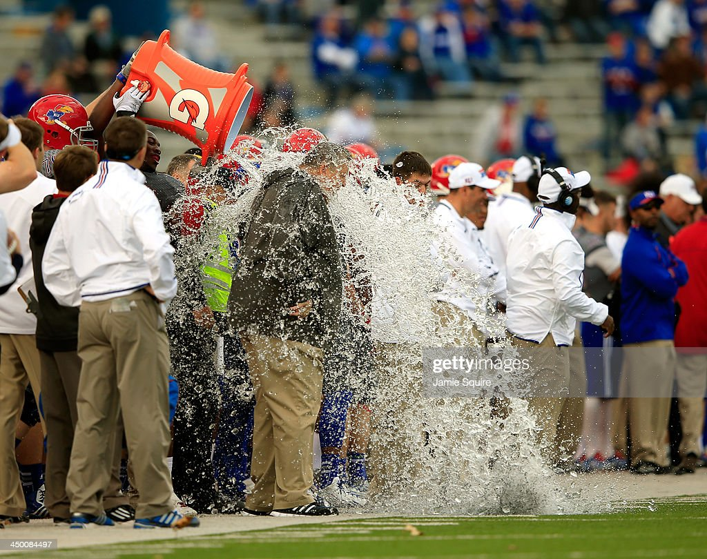 Head coach <a gi-track='captionPersonalityLinkClicked' href=/galleries/search?phrase=Charlie+Weis&family=editorial&specificpeople=631229 ng-click='$event.stopPropagation()'>Charlie Weis</a> of the Kansas Jayhawks is doused with water as the Jayhawks defeat the West Virginia Mountaineers 31-19 to win the game at Memorial Stadium on November 16, 2013 in Lawrence, Kansas.