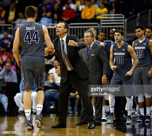 Head coach Chris Collins of the Northwestern Wildcats congratulates Gavin Skelly after Skelly scored during the CBE Hall Of Fame Classic game against...