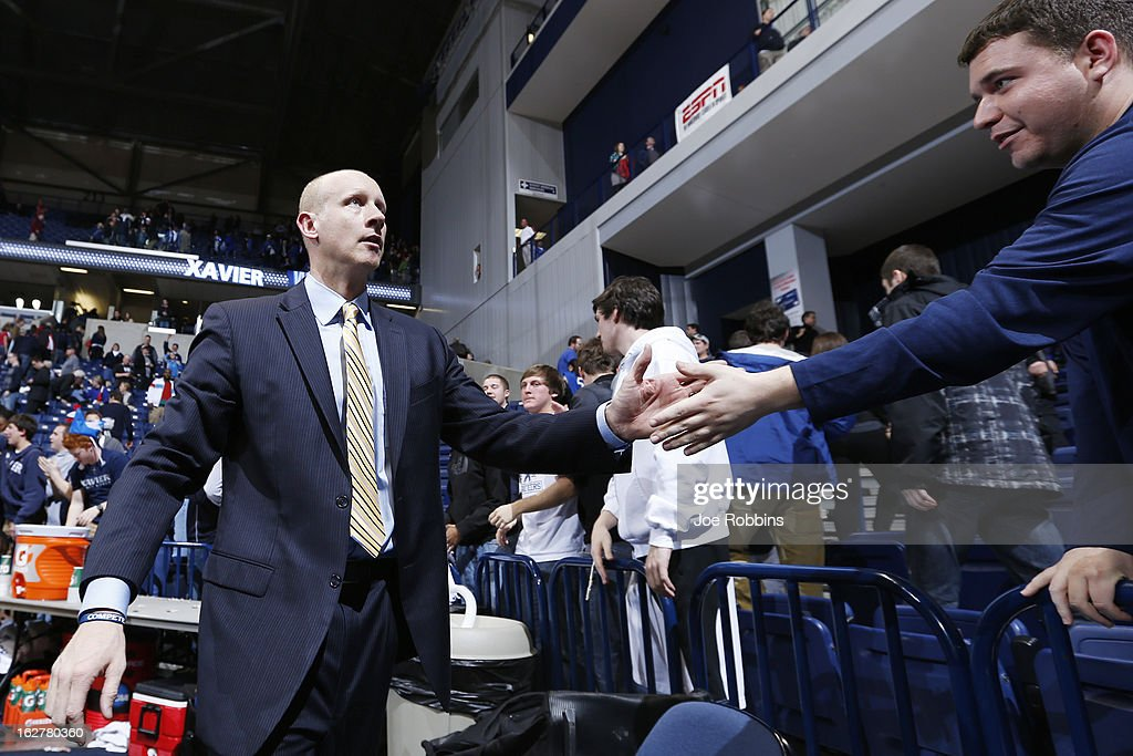 Head coach Chris Mack of the Xavier Musketeers celebrates with fans after the game against the Memphis Tigers at Cintas Center on February 26, 2013 in Cincinnati, Ohio. Xavier defeated Memphis 64-62.